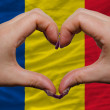 Stock Photo: Over national flag of romanishowed heart and love gesture made