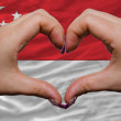 Over national flag of singapore showed heart and love gesture ma - Stock Photo