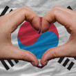 Over national flag of south korea showed heart and love gesture - Stock Photo