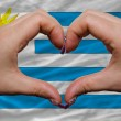 Over national flag of uruguay showed heart and love gesture made - Stock Photo