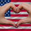 Over national flag of america showed heart and love gesture made - Stock Photo