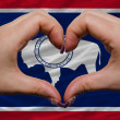 Over american state flag of wyoming showed heart and love gestur - Stock Photo