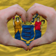 Over american state flag of new jersey showed heart and love ges - Stock Photo