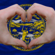 Over american state flag of nebraska showed heart and love gestu - Foto de Stock