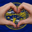 Stock Photo: Over americstate flag of nebraskshowed heart and love gestu