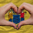 Stock Photo: Over americstate flag of new jersey showed heart and love ges