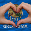 Stock Photo: Over americstate flag of oklahomshowed heart and love gestu