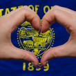 Stock Photo: Over americstate flag of oregon showed heart and love gesture