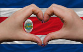 Over national flag of costa rica showed heart and love gesture m — Stock Photo