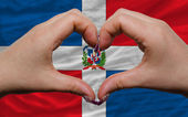 Over national flag of dominican showed heart and love gesture ma — Stock Photo