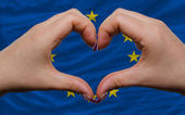 Over national flag of europe showed heart and love gesture made — Stock Photo
