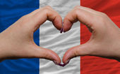 Over national flag of france showed heart and love gesture made — Stock Photo