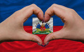 Over national flag of haiti showed heart and love gesture made b — Stock Photo