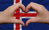 Over national flag of iceland showed heart and love gesture made — Stock Photo