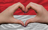 Over national flag of indonesia showed heart and love gesture ma — Stock Photo