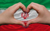 Over national flag of iran showed heart and love gesture made by — Stock Photo
