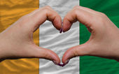 Over national flag of ivory coast showed heart and love gesture — Stock Photo