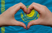 Over national flag of kazakhstan showed heart and love gesture m — Stock Photo