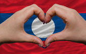 Over national flag of laos showed heart and love gesture made by — Stock Photo