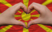 Over national flag of macedonia showed heart and love gesture ma — Stock Photo
