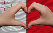 Over national flag of malta showed heart and love gesture made b — Stock Photo