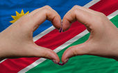 Over national flag of namibia showed heart and love gesture made — Stock Photo