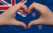 Over national flag of new zealand showed heart and love gesture — Stock Photo