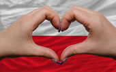 Over national flag of poland showed heart and love gesture made — Stock Photo