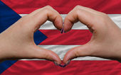 Over national flag of puerto rico showed heart and love gesture — Stock Photo