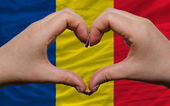 Over national flag of romania showed heart and love gesture made — Stock Photo
