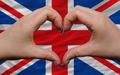 Over national flag of great britain showed heart and love gestur — Stock Photo