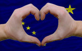 Over american state flag of alaska showed heart and love gesture — Stock Photo