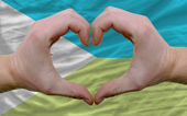 Over flag of djibuti showed heart and love gesture made by hands — Stock Photo