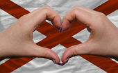 Over american state flag of alabama showed heart and love gestur — Stock Photo