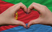 Over flag of eritrea showed heart and love gesture made by hands — Stock Photo