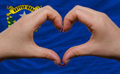 Over american state flag of nevada showed heart and love gesture — Stock Photo