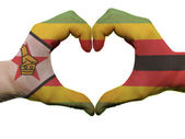 Heart and love gesture in zimbabwe flag colors by hands isolated — Stock Photo