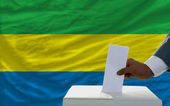 Man voting on elections in front of national flag of gabon — Photo