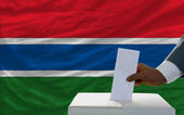 Man voting on elections in front of national flag of gambia — Стоковое фото
