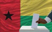 Man voting on elections in front of national flag of guinea biss — Zdjęcie stockowe