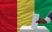 Man voting on elections in front of national flag of guinea — Zdjęcie stockowe