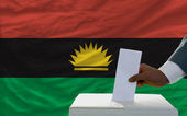 Man voting on elections in front of national flag of biafra — Стоковое фото