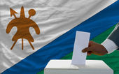 Man voting on elections in front of national flag of lesotho — Zdjęcie stockowe