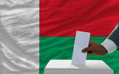Man voting on elections in front of national flag of madagascar — Zdjęcie stockowe