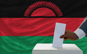 Man voting on elections in front of national flag of malawi — Stock Photo