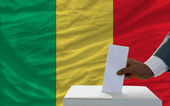 Man voting on elections in front of national flag of mali — Stockfoto