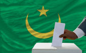 Man voting on elections in front of national flag of mauritania — Zdjęcie stockowe