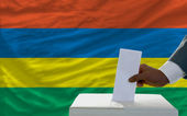 Man voting on elections in front of national flag of mauritius — Foto de Stock