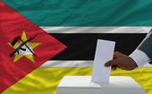 Man voting on elections in front of national flag of mozambique — Stock Photo