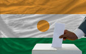 Man voting on elections in front of national flag of niger — Zdjęcie stockowe